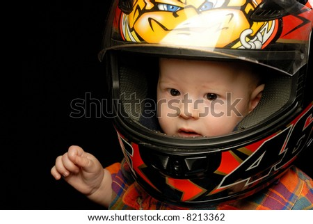 Close-up portrait of baby boy in motorcycle helmet holding right hand to his face - stock photo