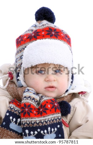 Close-up portrait of baby boy in winter wear in colorful scarf and cap - stock photo