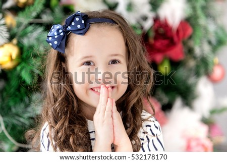 Close-up portrait of baby smiling girl which make a wish for the new year on the background of the Christmas tree. Holiday and fun. Happy baby girl. Merry Christmas. 2017