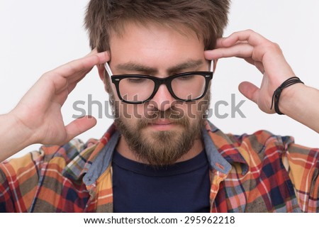 Close-up portrait of bearded man thinking. Man with brown hair touching his head with two hands for getting wonderful idea. - stock photo