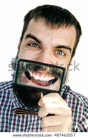 Close up portrait of bearded young man smiling and showing his teeth trough a magnifying glass on a white background.