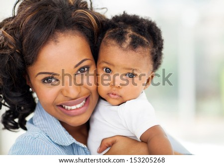 close up portrait of beautiful african mother and baby indoors - stock photo