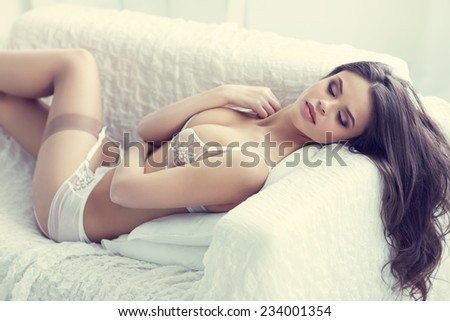 close up portrait of beautiful alluring young woman in white sexy lingerie lying in sofa - stock photo