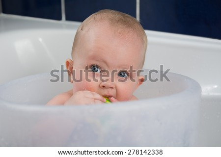 Close up portrait of beautiful baby having  bath and holding a toy in mouth - stock photo