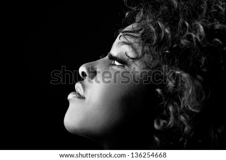Close up portrait of beautiful black woman on black background with red hair. Afro hairstyle. Studio shot - stock photo