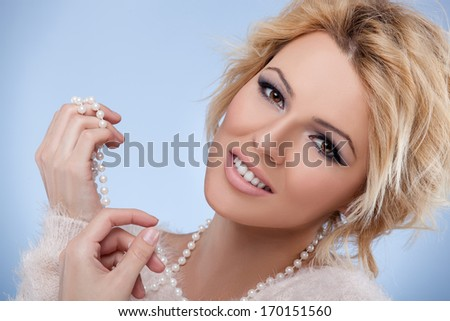 Close-up portrait of beautiful blonde girl with pearls