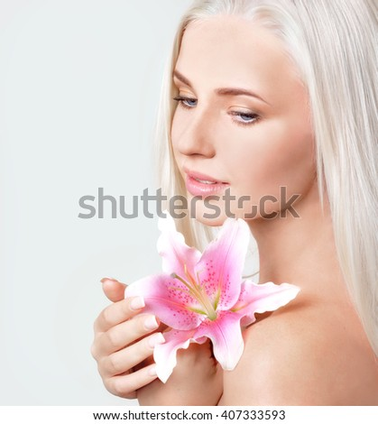 Close-up portrait of beautiful blonde with lily on gray background
