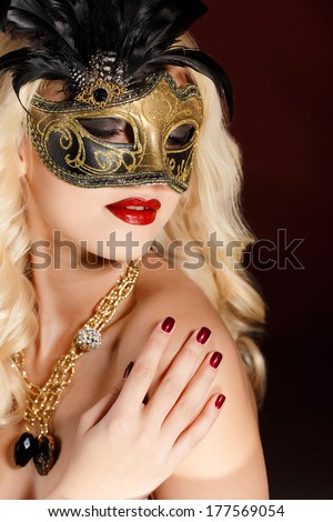 close-up portrait of beautiful blonde woman with bright make up hiding venetian carnival mask on dark background