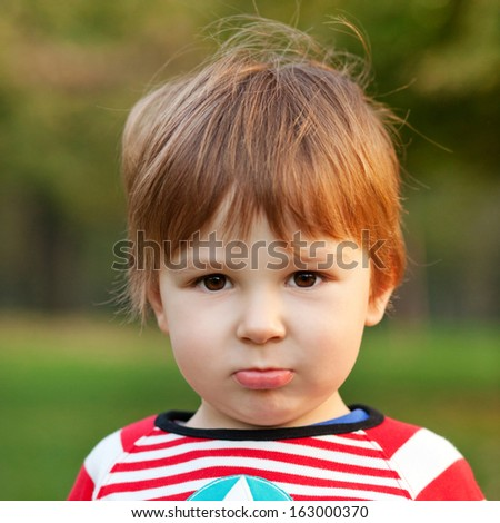 Close up portrait of beautiful boy pouting, shallow depth of field - stock photo