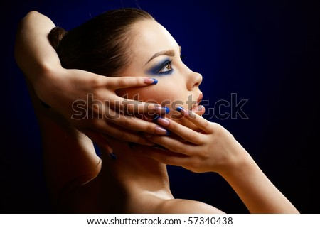 Close-up portrait of beautiful brunette with blue eye shadow make up and manicure