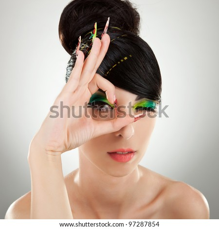 Close-up portrait of beautiful brunette with green and yellow eye shadow make up and manicure - stock photo