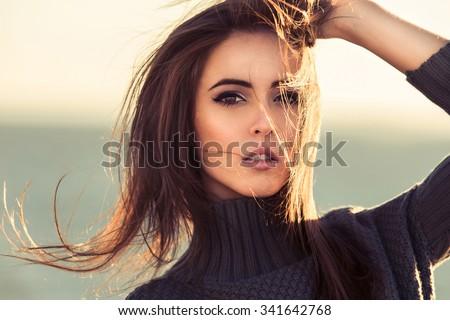 Close-up portrait of beautiful brunette woman outdoors - stock photo