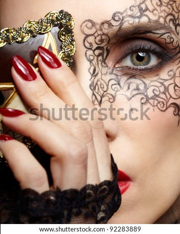 close-up portrait of beautiful brunette woman with facial body art hiding half of her face with carnival mask