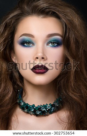 Close-up portrait of beautiful brunette woman with modern fashion make up. Smokey eyes and dark red lips. - stock photo
