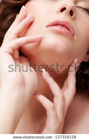 close-up portrait of beautiful brunette young woman with french manicure closing eyes - stock photo