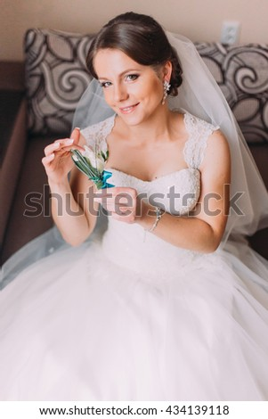 Close up portrait of beautiful caucasian mid adult bride sitting and holding cute little boutonniere - stock photo