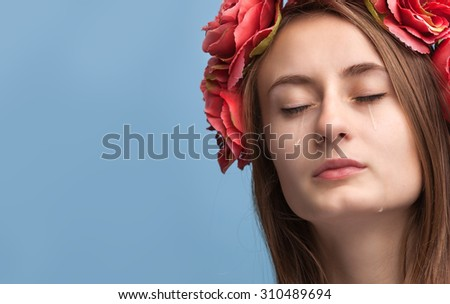 Close-up portrait of beautiful crying girl with tears on her cheeks and copy-space
