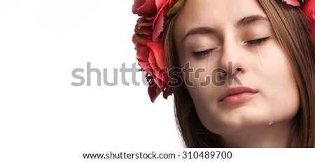 Close-up portrait of beautiful crying girl with tears on her cheeks isolated on white with copy-space