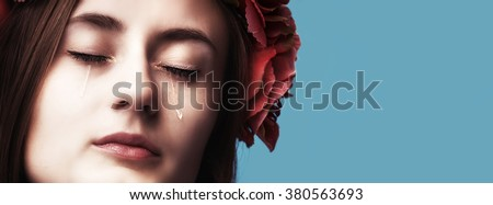 Close-up portrait of beautiful crying girl with tears on her cheeks on blue background with copyspace