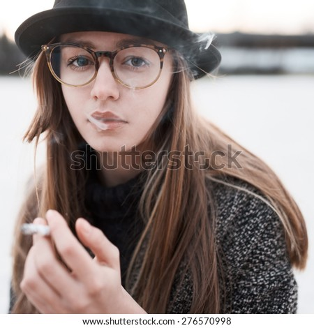 Close-up portrait of beautiful fashionable girl with a cigarette - stock photo