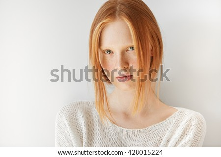 Close up portrait of beautiful freckled Caucasian teenage girl with red hair and blue eyes looking and smiling at the camera. Student girl posing against white copy space studio wall background - stock photo