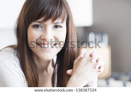 Close-up portrait of beautiful girl in her kitchen - stock photo