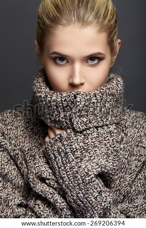 Close-up portrait of beautiful girl in knit sweater. - stock photo