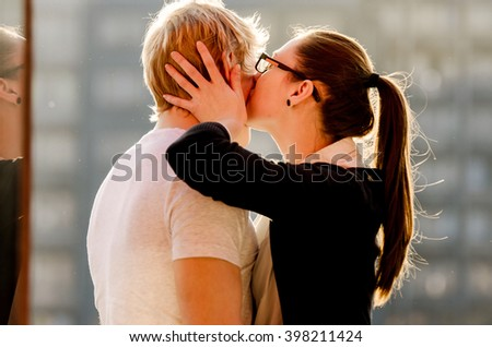 Close up portrait of beautiful girl kissing her girlfriend on cheek, photo with city background in last light of the sun. - stock photo