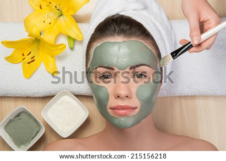Close-up portrait of beautiful girl looking at the camera with a towel on her head applying facial clay mask and beauty treatments lying on a table in spa near yellow flower and two plates - stock photo