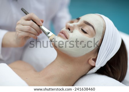Close-up portrait of beautiful girl with a towel on her head applying facial mask