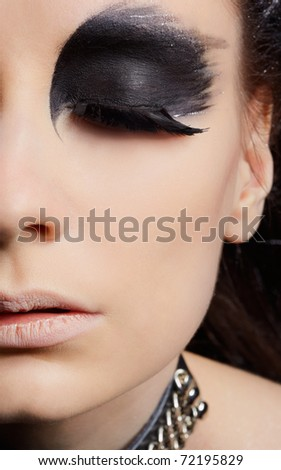 close-up portrait of beautiful girl with bird of prey fantasy make-up - stock photo