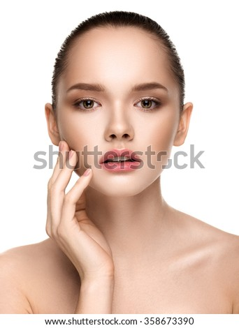 Close-up portrait of beautiful girl with clear healthy skin and nude make-up. Looking at the camera. Touching her face. Beauty studio shot. Isolated on white background. - stock photo