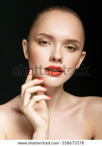 Close-up portrait of beautiful girl with clear healthy skin. Looking at the camera. Touching her face. Beauty studio shot over black background. - stock photo