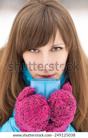 Close up portrait of beautiful girl with cup of coffee or hot tea. Young caucasian woman at winter outdoor - stock photo