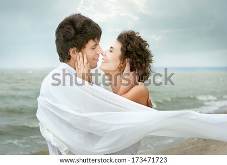 Close-up portrait of beautiful happy couple against gray sky