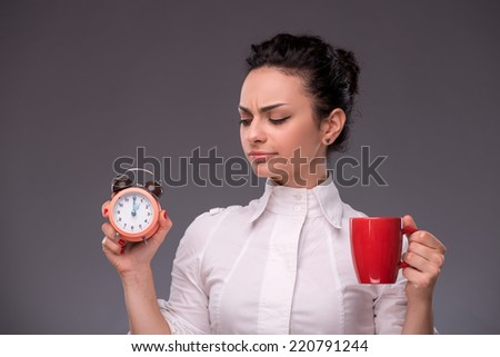 Close-up portrait of beautiful happy girl holding an alarm clock and a red cup in her hand and looking at it with suspicion isolated on grey background with copy place concept of time management - stock photo