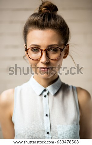 Close up portrait of beautiful hipster woman in trendy glasses looking to the camera. Gorgeous pretty sexy girl in eyeglasses. White urban wall background. Business, active, freedom lifestyle concept.