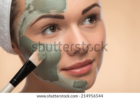 Close-up Portrait of beautiful looking aside girl in spa with a  towel on her head applying facial clay mask and beauty treatments with brush on her face isolated on beige background - stock photo