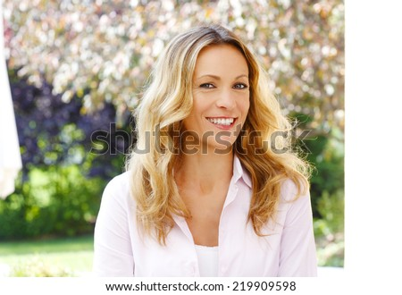Close-up portrait of beautiful mature woman sitting at garden. - stock photo