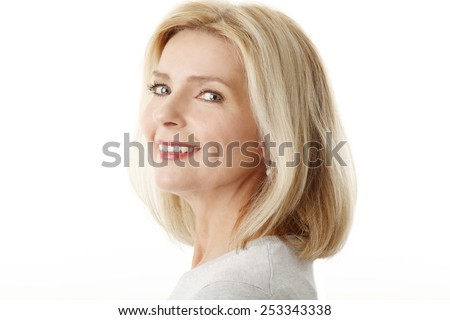 Close-up portrait of beautiful mature woman standing against white background.  - stock photo