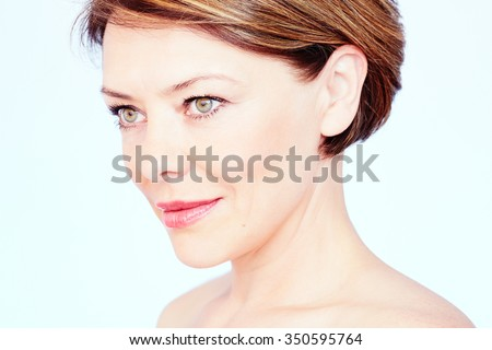 Close up portrait of beautiful middle aged woman with short brown hair, red lips and fresh makeup looking aside over blue background - beauty concept - stock photo