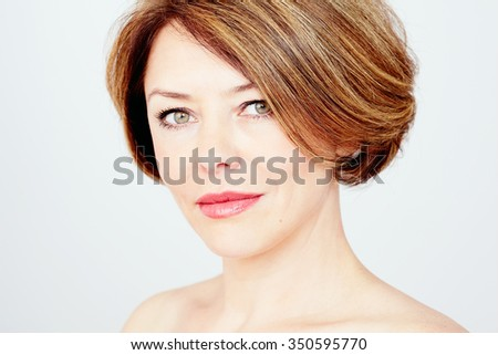 Close up portrait of beautiful middle aged woman with short brown hair, red lips and fresh makeup over white background  - beauty concept