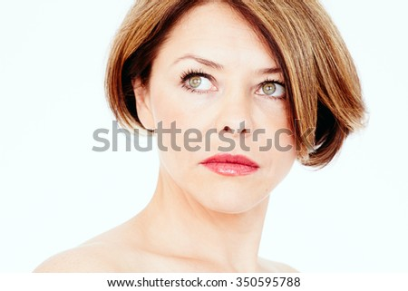 Close up portrait of beautiful middle aged woman with short brown hair, red lips and fresh makeup looking aside over white background - beauty concept - stock photo