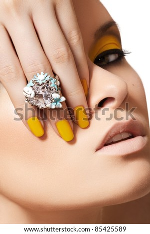 Close-up portrait of beautiful model face with neon yellow fashion make-up and with big crystal ring. Disco makeup and manicure, bright nail polish - stock photo