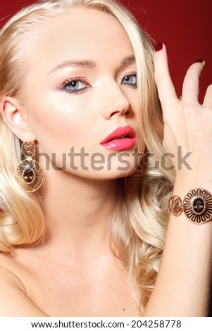 Close-up portrait of beautiful model with long blonde hair on red background and big lips