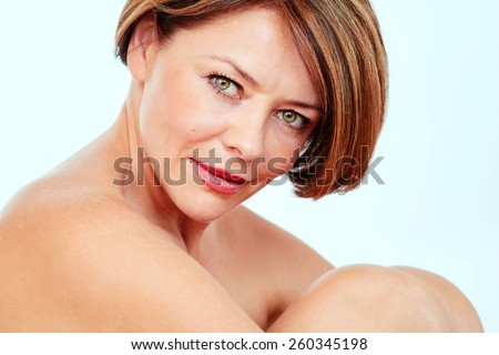 Close up portrait of beautiful nude mature woman hugging her knees - stock photo