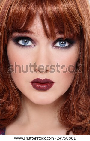 Close-up portrait of beautiful redhead girl with blue eyes and trendy makeup