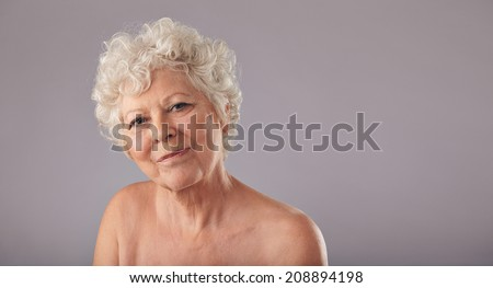 Close-up portrait of beautiful senior woman looking at camera with a smile on her face against grey background.  - stock photo