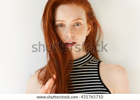 Close up portrait of beautiful sensual Caucasian young female with long loose red hair and perfect freckled skin looking at the camera with parted lips showing white teeth. Youth and beauty concept - stock photo