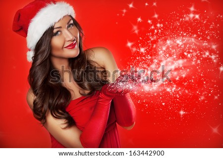 Close up portrait of beautiful sexy girl wearing santa claus clothes with snow in her hands, over red background - stock photo